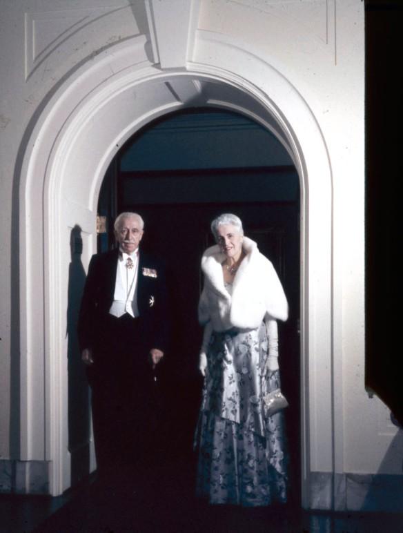 Photographie en couleur montrant un couple debout sous une porte d'arche en tenue de soirée regardant directement le photographe.