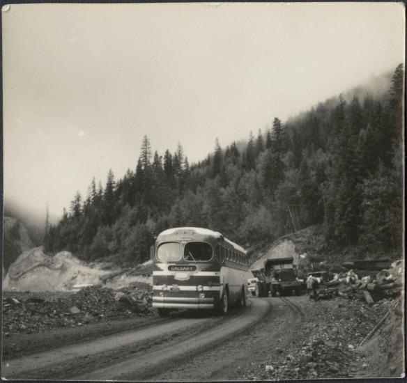 Photo noir et blanc d'un autobus public circulant sur une route en gravier dans une zone montagneuse. Il vient de dépasser une équipe d'ouvriers à l'arrière plan.