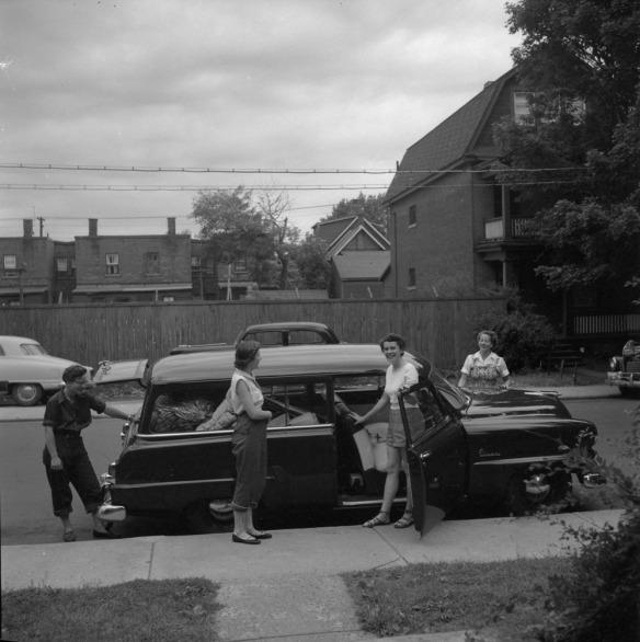 Photo noir et blanc de quatre femmes autour d'une voiture familiale remplie de bagages au début d'un road trip.