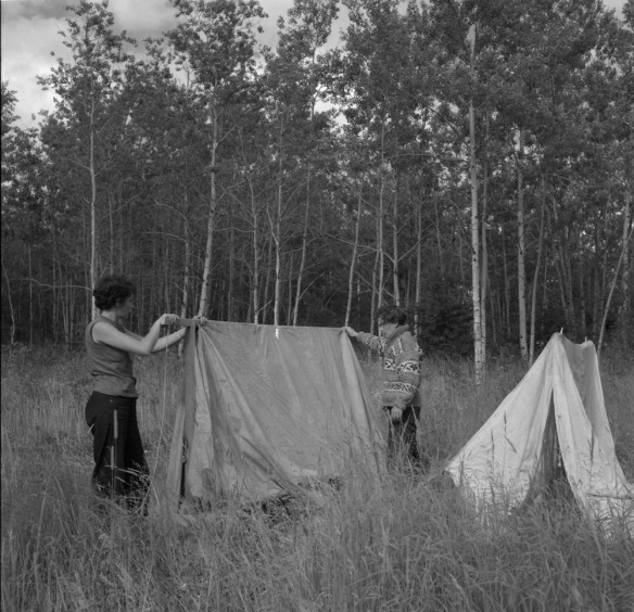 Photo noir et blanc de deux femmes installant deux tentes dans un pré entouré d'arbres où pousse du long gazon.