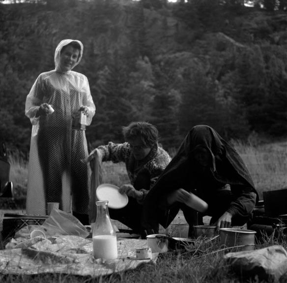 Photo noir et blanc de trois femmes préparant un repas sous la pluie dans un bois