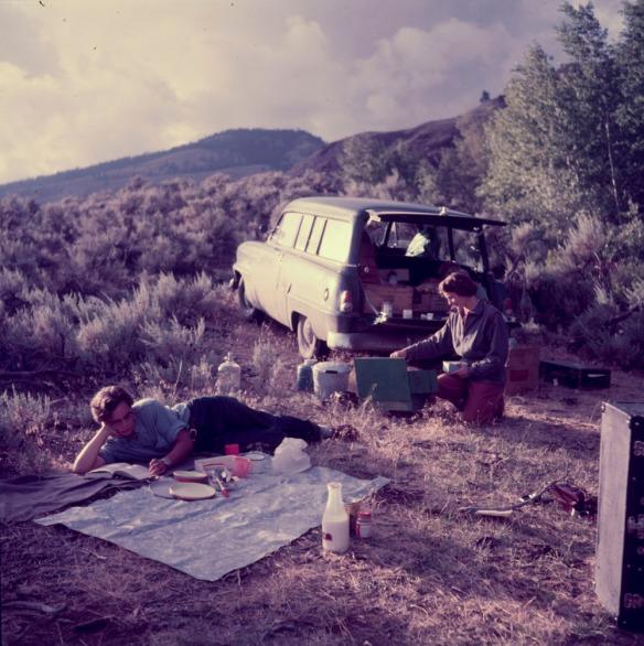 Photo couleur montrant deux femmes sur un terrain gazonné, avec des montagnes à l'arrière plan. Une d'entre elles est couchée sur le côté et lit sur une nappe à pique nique tandis que l'autre est à genoux près d'un réchaud installé derrière une voiture familiale.