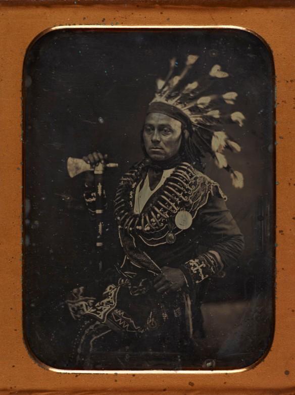 Un portrait de Maungwudaus, vêtu d'une tenue cérémoniale comprenant une coiffe de plume et ses deux médailles.