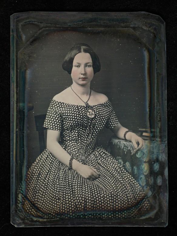 Le portrait, colorié à la main, d'une femme assise vêtue d'une robe à pois.