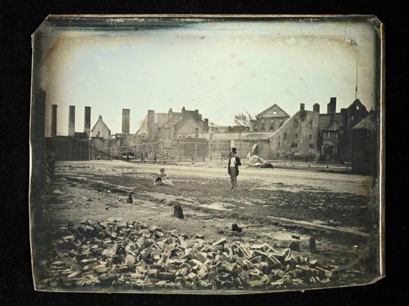 La photo d'un homme debout et d'une femme assise, parmi les ruines de la brasserie.