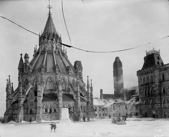 Photo noir et blanc d'un édifice circulaire à l'architecture complexe ayant des pinacles et des arcs-boutants. C'est l'hiver, et l'édifice à côté est partiellement couvert de glace. Des pompiers éteignent un incendie.