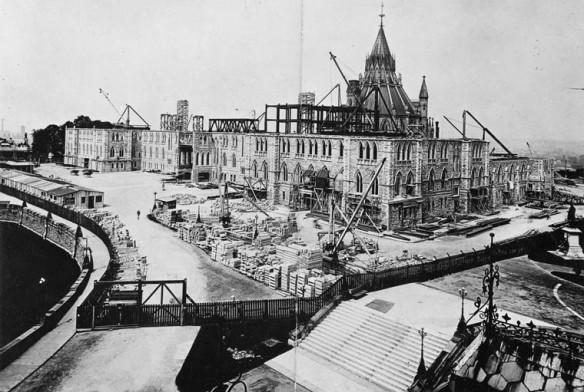 Photo noir et blanc montrant les trois premiers étages d'un édifice. La rotonde de la Bibliothèque du Parlement est à l'arrière plan. Le site est entouré de grues et de matériaux de construction.