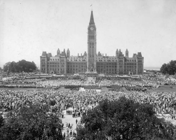 Photo noir et blanc montrant la façade avant de l'édifice du Centre. La foule se masse sur la Colline du Parlement.