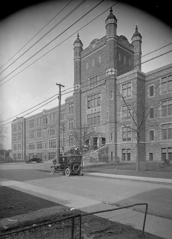 Photo en noir et blanc montrant l'entrée d'un bâtiment. Deux véhicules sont garés en avant et quelques personnes se tiennent à l'entrée.