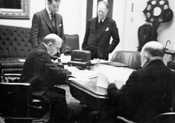 Photo en noir et blanc, un peu floue, de quatre personnes en costume, dans un bureau, autour d'une table couverte de documents. Deux personnes sont assises et examinent des documents, alors que les deux autres sont debout et surveillent les procédures.