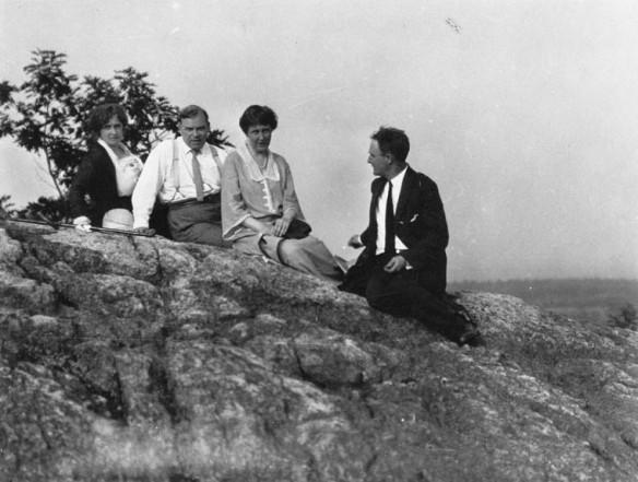 Photo en noir et blanc d'un groupe de personnes assises sur une haute barre rocheuse, devant des arbres flous et un arrière-plan distant. Chacun regarde en direction du photographe, sauf un homme qui regarde les autres.