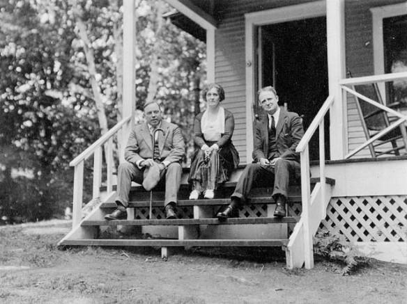Photo en noir et blanc de trois personnes assises sur les marches d'escalier d'un chalet et regardant en direction du photographe.