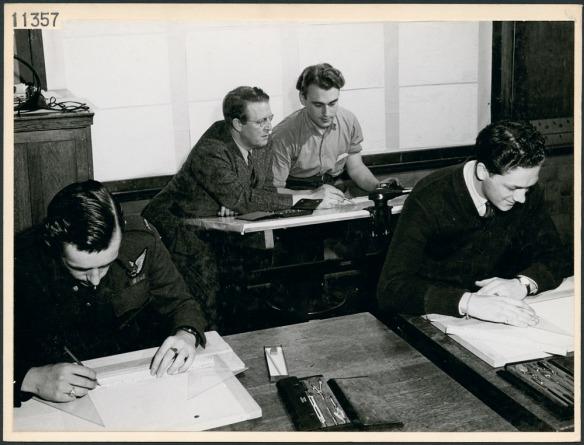 Photo en noir et blanc montrant des étudiants dans une salle de classe d'une école technique et un enseignant travaillant avec un étudiant.