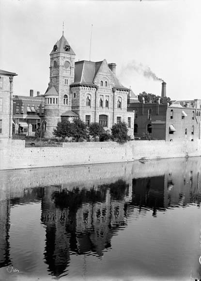 Photo en noir et blanc d'un bâtiment aux allures de château, surplombant un cours d'eau rappelant une douve.
