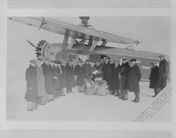 Une photographie en noir et blanc illustrant un groupe d'hommes vêtus de manteaux d'hiver et de chapeaux devant un avion monomoteur. Les hommes sont debout, en demi-cercle, et font face à l'appareil-photo. Des sacs de courrier-avion reposent sur le sol.