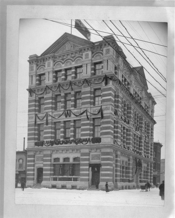 Photo en noir et blanc d'un édifice décoré pour Noël, bordé d'une rue enneigée. La façade, très travaillée, révèle plusieurs couches alternées de pierres et de briques.