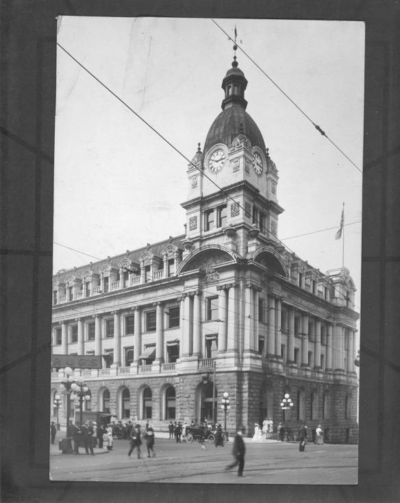 Photo en noir et blanc d'un bâtiment richement travaillé, dont l'un des angles est coiffé d'une grande tour d'horloge. On aperçoit au premier plan des gens et des voitures.