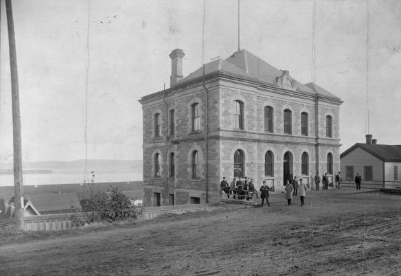 Photo en noir et blanc d'un bâtiment de deux étages devant lequel se tiennent des gens.