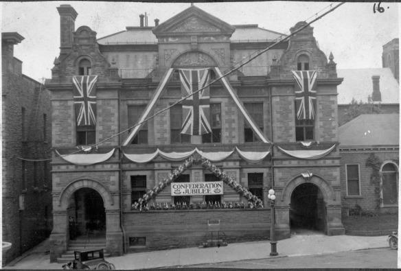 Photo en noir et blanc d'un bâtiment orné de drapeaux du Royaume-Uni et d'un panneau sur lequel on peut lire Confederation Jubilee.