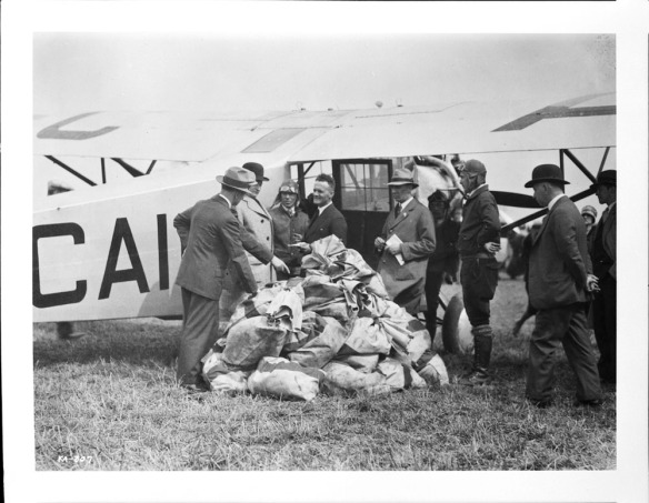 Une photographie en noir et blanc d'un groupe d'hommes debout devant un avion monomoteur. Les hommes sont placés en demi-cercle autour de nombreux sacs de courrier empilés sur le sol.