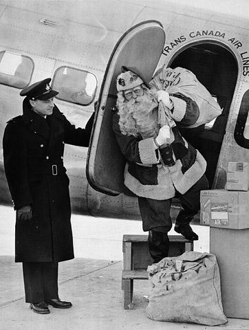 Une photographie en noir et blanc illustrant un homme costumé en père Noël qui sort de l'avion par la porte latérale en transportant un sac de courrier-avion. Il se tient sur un marchepied portatif, prêt à fouler le sol. Un homme en uniforme tient la porte ouverte.