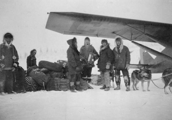 Une photographie en noir et blanc illustrant des hommes qui se tiennent debout sous l'aile d'un avion, à côté d'un traîneau à chiens chargé de sacs de courrier-avion. La plupart des hommes prennent la pose, faisant face à la caméra. On peut voir des chiens attelés à un traîneau.