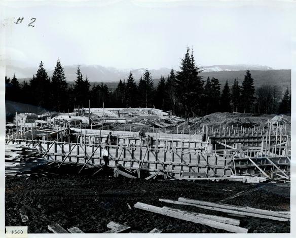 Photographie en noir et blanc d'un chantier de construction montrant des structures en bois et des échafaudages.