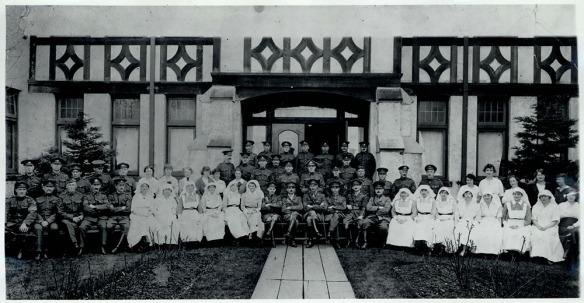 Photographie en noir et blanc d'hommes en uniforme et d'infirmières assis dans un vestibule somptueux de style élisabéthain.