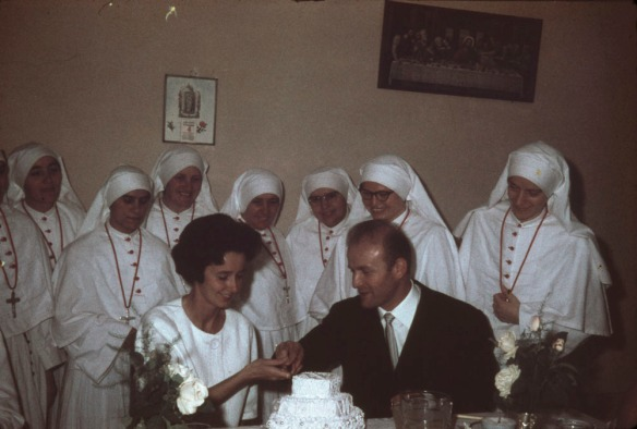 Une photographie en couleur montrant un groupe d'infirmières entourant deux personnes qui s'apprêtent à couper un gâteau de mariage.