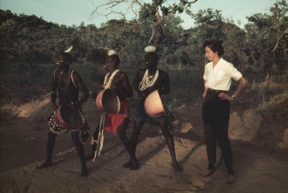 Une photographie en couleur montrant quatre personnes à l'extérieur. Trois d'entre elles portent une tenue ougandaise traditionnelle alors que la quatrième est vêtue à l'occidentale.
