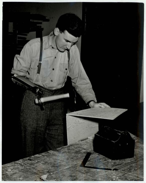 Photographie en noir et blanc d'un homme tenant un marteau avec sa prothèse pour assembler deux morceaux de bois.