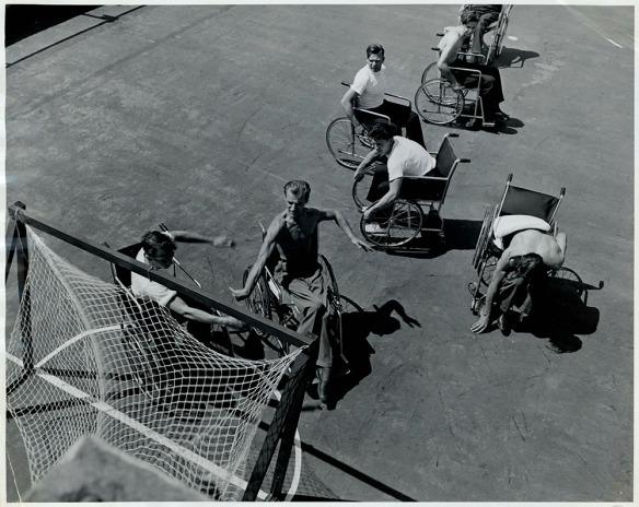 Photographie en noir et blanc montrant sept hommes en fauteuil roulant qui jouent à un jeu avec une balle autour d'un filet ressemblant à un filet de hockey.