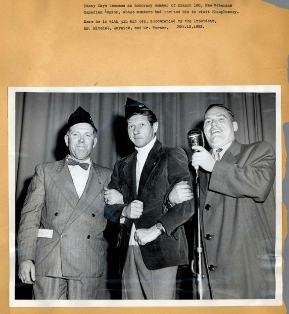 Photographie en noir et blanc placée sur une feuille de papier montrant trois hommes bras dessus, bras dessous autour d'un micro. La photo comporte une légende.