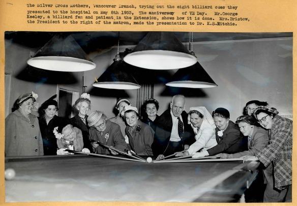 Photographie en noir et blanc montrant un grand groupe de femmes et un homme autour d'une table de billard. Certaines personnes sont penchées vers la table et pointent vers les boules de billard avec des baguettes. La photo comporte une légende.