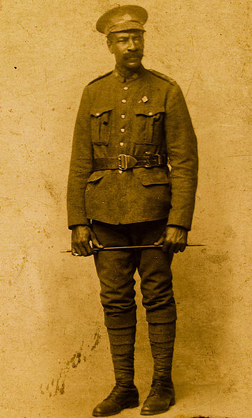 Une photo sépia d'un homme en uniforme portant une ceinture et une casquette d'officier et tenant un bâton dans ses deux mains devant le haut de ses cuisses.