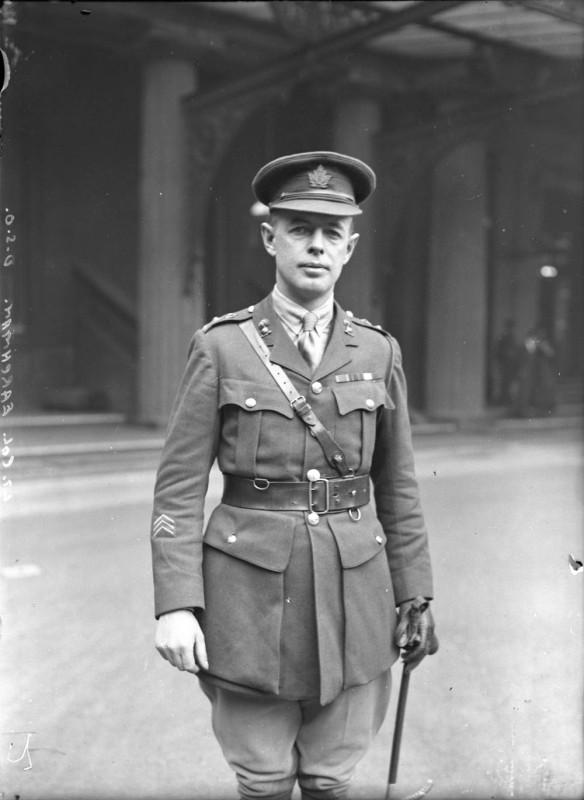 Photo en noir et blanc d'un homme debout, vêtu d'un uniforme, d'une casquette et d'un ceinturon-baudrier, une canne à la main.