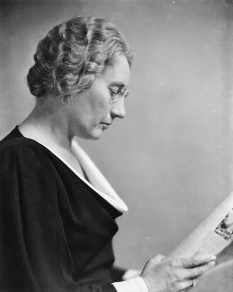 Une photographie en noir et blanc d'Agnes Macphail, de profil, lisant le journal
