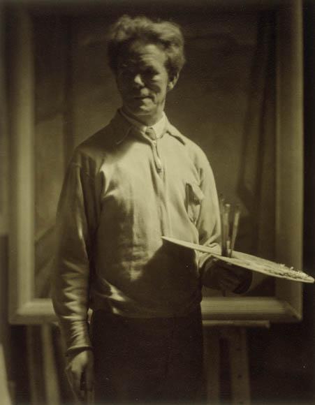 Photographie en noir et blanc montrant un homme, debout, tenant une de la peinture et des pinceaux dans une main avec le regard un peu à l'écart.