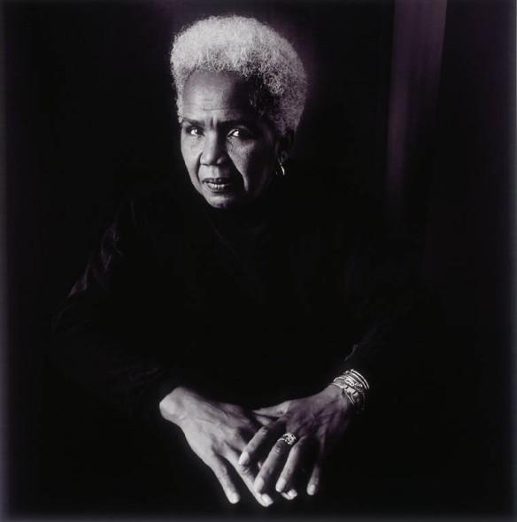 Une photographie en noir et blanc de Rosemary Brown assise derrière un bureau, ses mains reposant sur celui-ci.