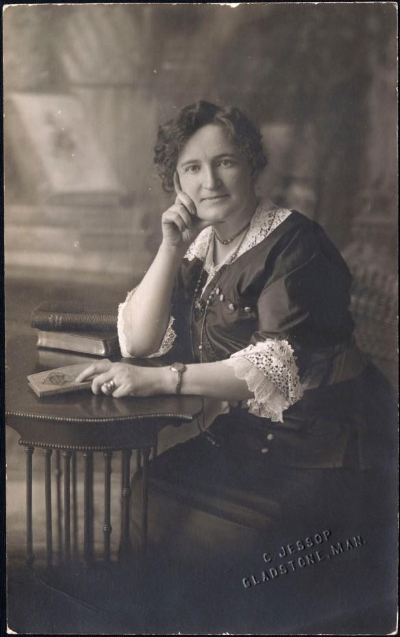 Photo en noir et blanc d'une femme assise, accoudée sur une table, la tête appuyée sur sa main droite, un livre dans sa main gauche. Elle regarde l'objectif.