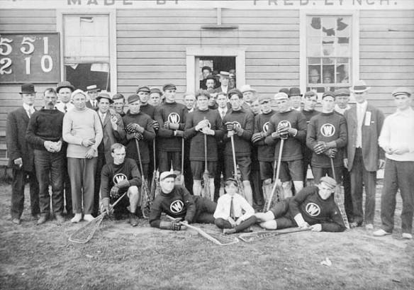 Photographie en noir et blanc de l'équipe de crosse de New Westminster. Les hommes sont debout, à genou ou couchés sur le côté devant un petit bâtiment. Les joueurs portent l'uniforme de l'équipe et tiennent leur bâton de crosse. Aussi sur la photo, des hommes et un petit garçon en tenue de ville.
