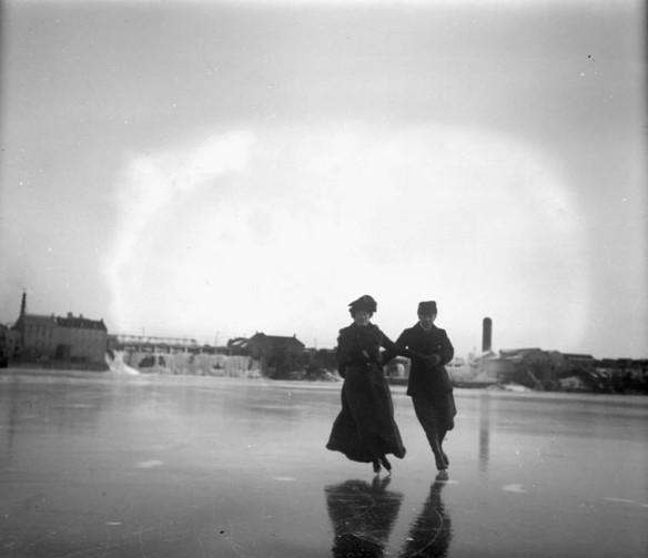 Photographie en noir et blanc représentant un couple qui patine ensemble en se tenant la main, habillé de vêtements d'hiver. En arrière-plan, on voit des bâtiments et d'autres structures.