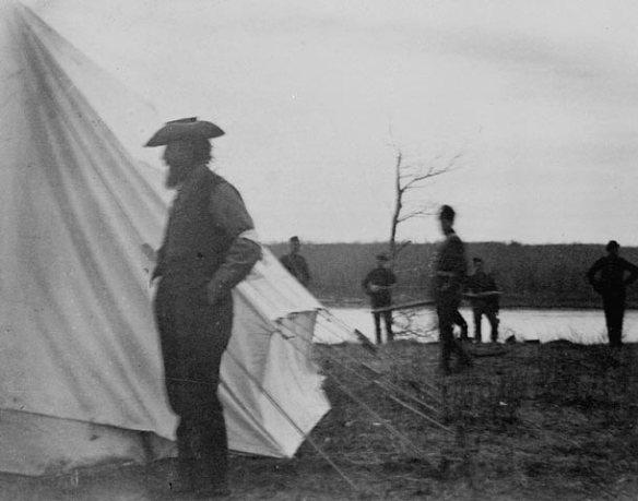 Photographie en noir et blanc du profil d'un homme debout, devant une tente blanche. En arrière-plan, cinq hommes debout.