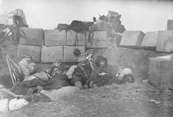 Photographie en noir et blanc de cinq hommes endormis, étendus sur le sol derrière une barricade faite de terre et d'un amoncellement de fournitures.