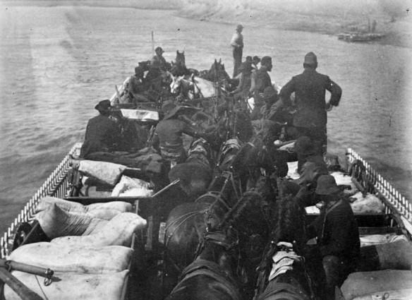 Photographie en noir et blanc d'hommes, de chevaux et de fournitures à bord d'un traversier sur la rivière Saskatchewan Sud.