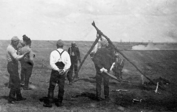 Photographie en noir et blanc de six hommes debout autour de la carcasse d'un animal suspendue à un trépied fait de branches.