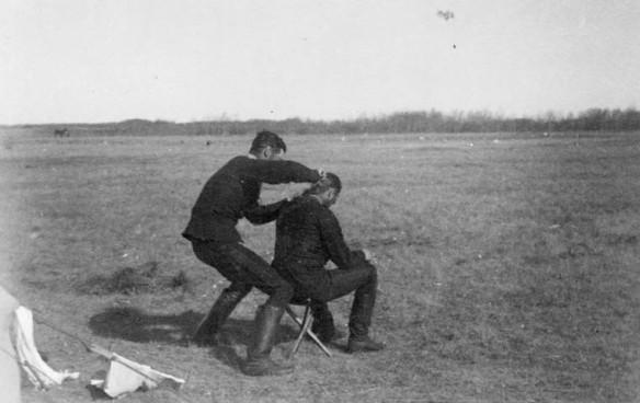 Photographie en noir et blanc d'un soldat qui coupe les cheveux d'un soldat assis dans un champ.
