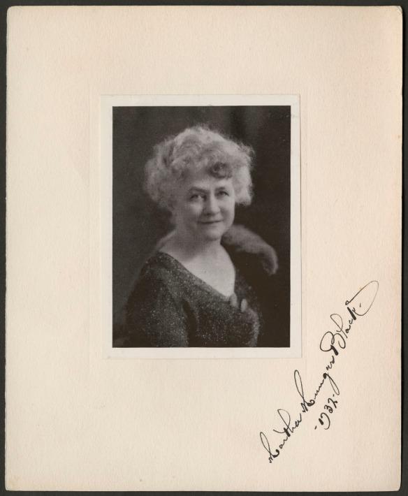 Photographie en noir et blanc signée, doublée d'un passe-partout et arborant une femme qui sourit, datée de 1932.