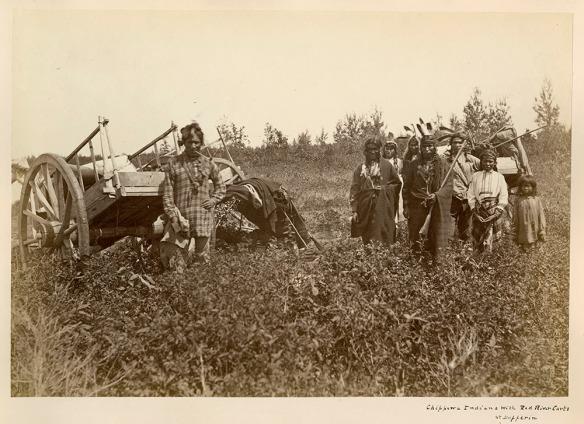Photo noir et blanc montrant un homme vêtu à l'européenne, debout à gauche devant une charrette de la rivière Rouge. À droite, un groupe d'hommes, de femmes et d'enfants portant des vêtements traditionnels des Premières Nations sont debout devant une autre charrette de la rivière Rouge.