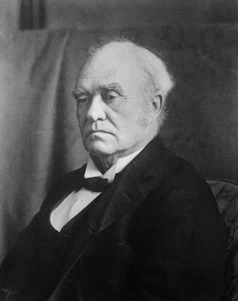 Photographie en noir et blanc d'un vieil homme portant une veste de soirée avec une chemise blanche et une cravate noire.